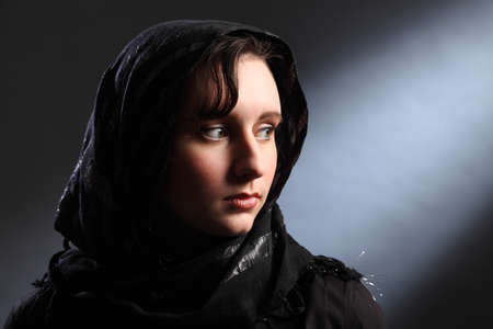 Peaceful and serene lighting of beautiful young woman wearing black hijab, looking away over her shoulder. photo