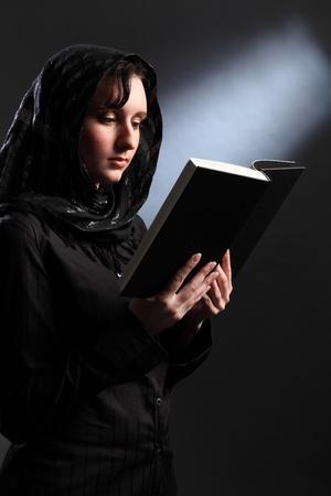 Beautiful young woman wearing black headscarf reading the bible in church. photo