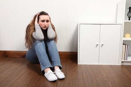 alarmed: Teenage girl sitting on the floor at home, looking scared and frightened, holding her head in her hands.