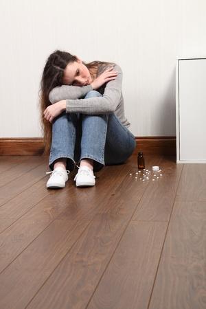overdosering: Teenage meisje zitten op de vloer in huis, op zoek bang en angstig. Heeft haar hoofd naar beneden en een fles pillen op de grond naast haar.