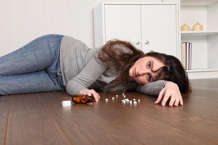 medicine cabinet: Teenage girl lying on the floor at home, alone with a blank expression on her face. There is a bottle of pills on the floor beside her.