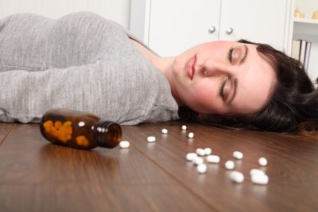 túladagolás: Young woman lying on the floor at home after an overdose of pills. Her eyes are closed and there is a bottle of pills on the floor beside her.