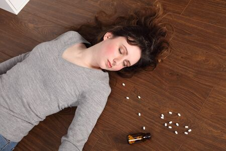 Young woman lying on the floor at home after an overdose of pills. Her eyes are closed and there is a bottle of pills on the floor beside her. photo