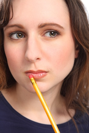 Young caucasian woman with beautiful bright eyes, holding pencil against her chin while deep in thought. photo
