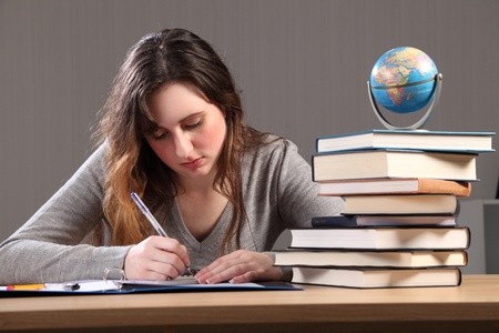 Young caucasian student girl at home, sitting to her desk studying with work books nearby and a globe of the world. photo