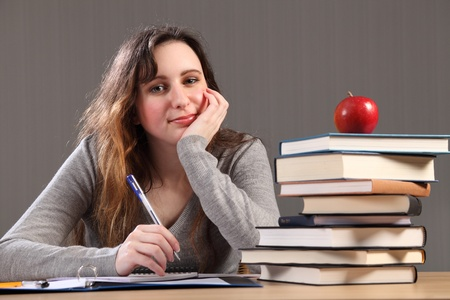 Young caucasian student girl at home, sitting to her desk studying with work books nearby and a red apple. photo