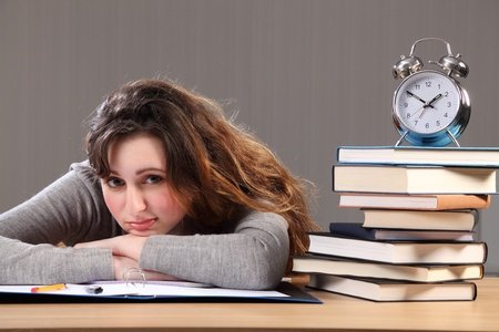 break time: Time for a break for young caucasian student girl doing her homework. She is sitting resting chin on desk with study work books and a clock nearby. Stock Photo