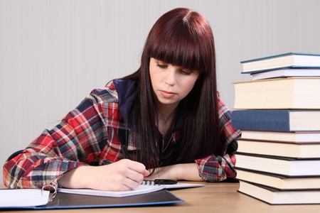 Young caucasian student girl at home, sitting to her desk studying with work books nearby. photo