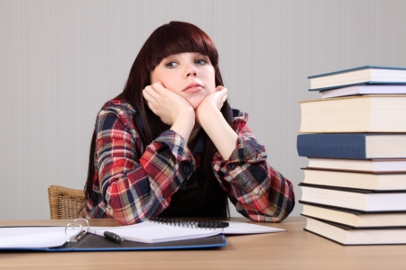 Young caucasian student girl at home, sitting to her desk with head resting on hands looking tired, taking a break from doing homework. photo