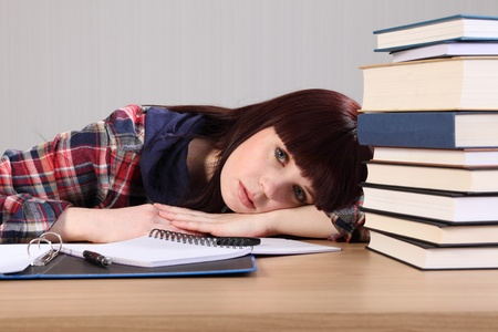 Young caucasian student girl at home, with head resting on her desk looking tired, taking a break from doing homework. photo