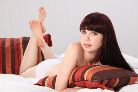 A beautiful young woman lying in bed, wearing only underwear briefs. She is lying on her front hugging a cushion. photo