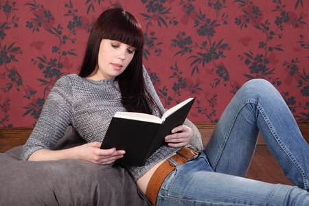 Beautiful young caucasian girl wearing blue jeans and casual knitted top, sitting on a bean bag at home, reading a book. She has long black hair with a red tint. photo