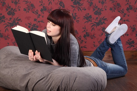 Casual and relaxed a beautiful young caucasian girl wearing blue jeans and knitted top, lying on a bean bag at home on the floor, reading a book. She has long black hair with a red tint. photo