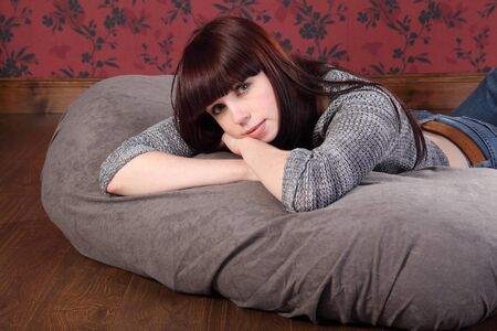 Casual and relaxed a beautiful young caucasian girl wearing blue jeans and knitted top, lying on a bean bag at home on the floor. She has long black hair with a red tint. Stock Photo - 9746858