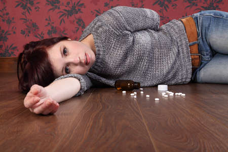 self harm: Teenager girl lying on the floor at home after an overdose of pills. Her eyes are open and there is a bottle of pills on the floor beside her.