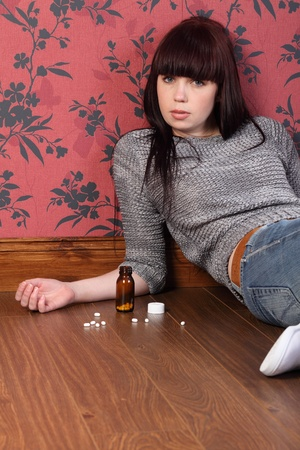 Teenager girl lying on the floor at home contemplating suicide. Her eyes are open staring straight to camera and there is a bottle of pills on the floor beside her. photo