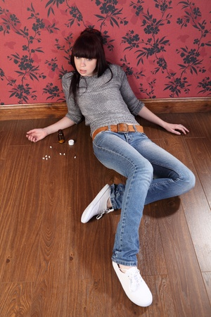 cry for help: Teenager girl lying on the floor at home contemplating suicide. Her eyes are open staring straight to camera and there is a bottle of pills on the floor beside her. Stock Photo