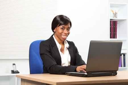 Beautiful young African American woman working in office looking up from her laptop with a lovely smile Stock Photo - 9746686
