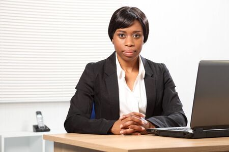 Beautiful young African American woman working in office sitting to her desk with a seus, stern expression. Stock Photo - 9746689