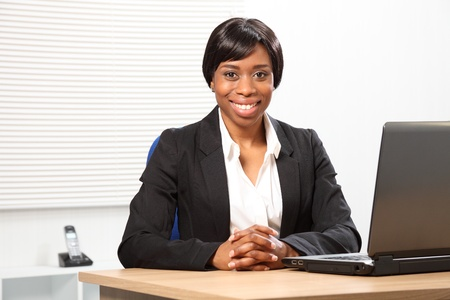 at her desk: Happy young black woman working in office sitting to her desk with a beautiful smile