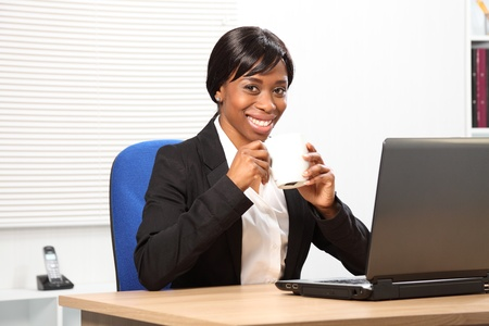 Beautiful young black woman enjoying her coffee while working in the office. She has a happy smile and is sitting in front of a laptop wearing a dark business suit. photo
