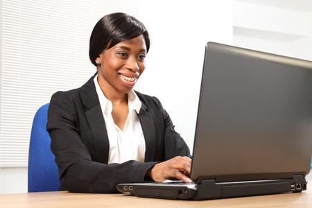 secretaria sexy: Feliz joven mujer negra en la Oficina, sentado en su escritorio con su port�til, con una hermosa sonrisa. Fotograf�a de �ngulo bajo, mirando hacia arriba. Foto de archivo