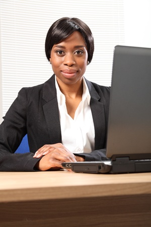 Beautiful young black black business woman working in office sitting to her desk using her laptop, with a serious expression on face. Picture taken from low angle looking upwards. photo