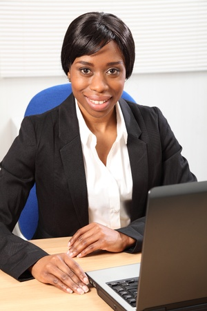 black secretary: Happy young black woman working in office sitting to her desk using her laptop, with a beautiful smile. Picture taken from high angle looking downward.