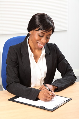 Happy young black woman working in office sitting to her desk signing a document. She is looking down at the paper with a beautiful smile. Picture taken from high angle. Stock Photo - 9746759