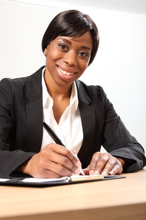Happy young black woman working in office sitting to her desk signing a document. She is looking down to the camera with a beautiful smile. Picture taken from low angle. photo