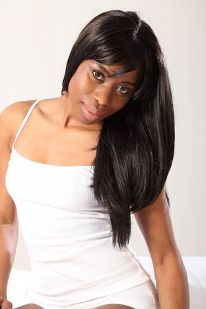 african american woman: Beautiful young African American woman with a sensual smile, sitting casually in bed wearing white underwear and vest, with long black hair. Stock Photo