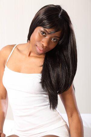 unterwäsche frau: Sch�ne junge afroamerikanische Frau mit einem sinnlichen L�cheln, sitzt l�ssig im Bett tragen wei�e Unterw�sche und Weste, mit langen schwarzen Haaren.