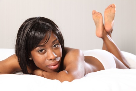 Beautiful young topless African American woman lying casually in bed, very relaxed with chin resting on her hands. Stock Photo - 9746714