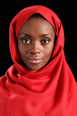 Tranquil portrait of beautiful young black woman wearing red hijab, taken against a black background. photo