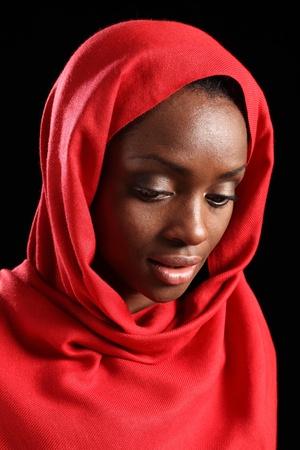 mujeres musulmanas: Hermosa negra estadounidense musulm�n joven hiyab rojo, ojos mirando hacia abajo adoptadas contra un fondo negro.
