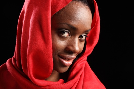 Headshot of beautiful young black muslim girl wearing red hijab, with a happy smile on her face. photo