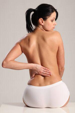 femme nue: Bas lombalgie et mal pour la belle jeune femme portant knickers blancs avec un dos nu.