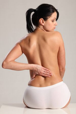 naked woman back: Lower back pain and ache for beautiful young woman wearing white knickers with a naked back. Stock Photo