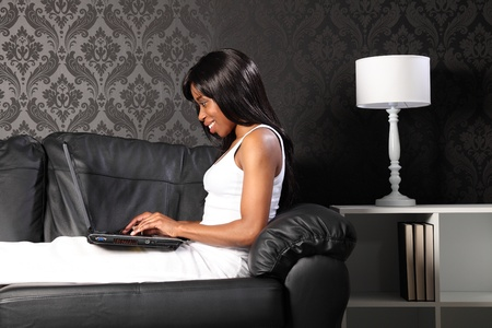 Beautiful smiling young black woman sitting on leather sofa at home, surfing the internet with her laptop. photo