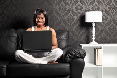 Hermosa sonriente joven mujer negra Cruz legged sentado en el sof� de cuero en casa, navegar por internet con su equipo port�til.