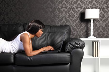 Beautiful smiling young african american woman lying on black leather sofa at home, surfing the internet with her laptop computer. photo