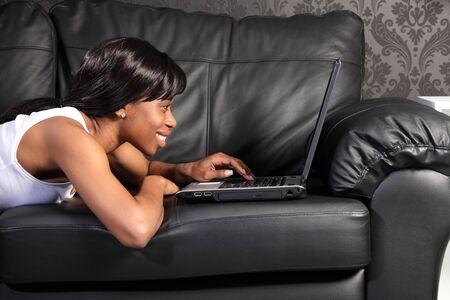Hermosa sonriente joven mujer afroamericana tirado en el sof� de cuero negro en casa, facebook de navegaci�n en internet con su equipo port�til.