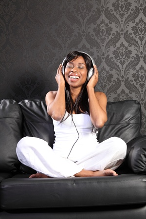 Beautiful smiling young african american woman sitting on black leather sofa at home, headphones on listening to music. photo