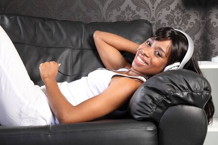 Beautiful smiling young african american woman lying on black leather sofa at home, headphones on listening to music. photo