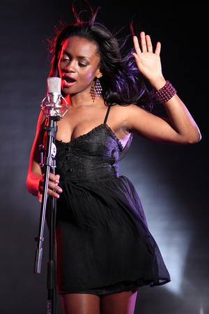 singing: Beautiful black girl on stage with microphone singing, wearing a black dress and purple bead bracelet. Stock Photo