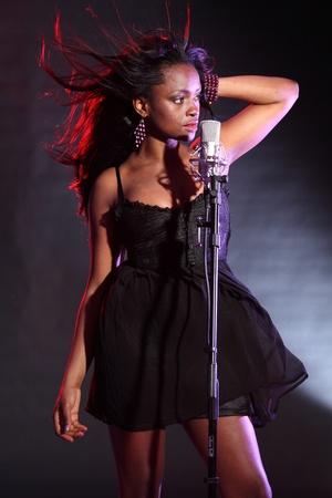 Afroamericana chica sexy en el escenario con canto de micr�fono, luciendo un vestido negro y pulsera Perla p�rpura. Su pelo sopla volver con efecto de viento.