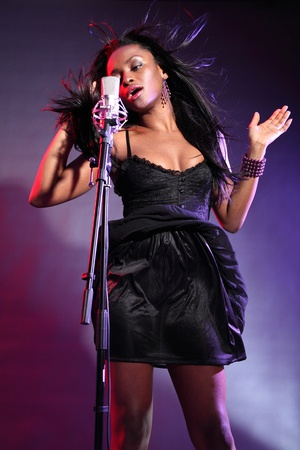 stage performer: Sexy african american girl on stage with microphone singing, wearing a black dress and purple bead bracelet. Her hair is blowing back with wind effect and she is concentrating deeply on her song. Stock Photo