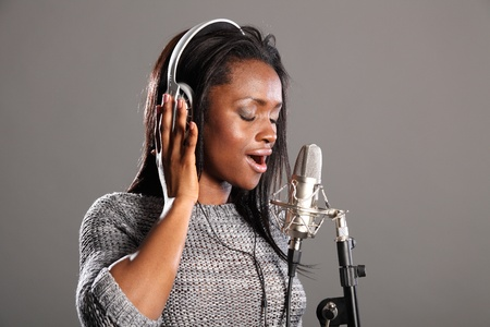 Beautiful young african american woman with eyes closed, wearing headphones and singing into microphone in recording studio. photo