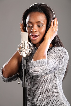 Beautiful young black girl wearing headphones and singing into microphone in recording studio. photo