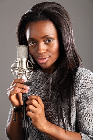 Happy beautiful young black woman singer in the recording studio taking a relaxing break. She is standing next to microphone. photo